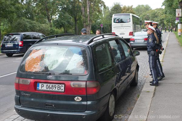 """Freitag, 11. September 2015: In der Schüttelstraße in Wien-Leopoldstadt, der Einfahrtsstraße aus dem Osten Österreichs, kontrollieren Polizeibeamte Autobusse und Personenautos. Der Grund: Tausende Flüchtlinge strömen aus Ungarn nach Wien. """"Die Menschen, die zu uns kommen, sind arm. Wir wollen aber die Schlepper aus dem Verkehr ziehen, die aus der Not der Menschen ein Millionengeschäft machen"""", sagt ein Polizist."""