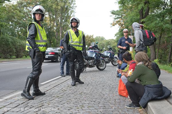 Die Menschen werden eingeladen, auf dem Gehsteig Platz zu nehmen, um sich während der organisatorischen Kommunikation der Polizei auszuruhen. Sie essen Bananen und Äpfel, die sie mitgebracht haben, lächeln freundlich und bieten auch den Polizisten und dem Fotografen Früchte an.